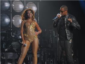 Two people are performing on stage. The woman at left wears a pink short dress, transparent stockings, and she holds a microphone with her right hand. She is looking something at her right while she holds her left on her hip. The man at right is talking through a microphone. He wears a jacket, a shirt and pants, all of them dark.