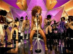 A female is singing and dancing. She wears a golden dress and heels of the same color. Behind her, a band is playing their instruments.