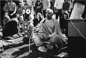A black-and-white photo of the swami sitting cross-legged with a figure of round-eyed smiling deity to his right