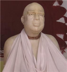 A face close-up of a marble statue of a man with wooden beads and white cloth around the neck.