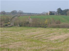 A few buildings scattered amongst fields and trees.
