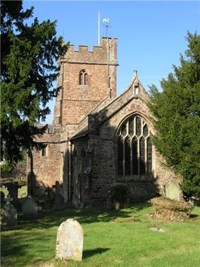 Stone building with arched windows and square tower.