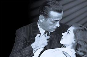 Black-and-white image of a man and a woman, seen from mid-chest up, their faces in profile, gazing into each other's eyes. He embraces her in a dip with his right arm and holds her right hand to his chest with his left hand. He wears a pin-striped suit and a dark tie. She wears a white top. On the left, the background is black; on the right, it is lighter, with a series of diagonal shadows descending from the upper corner.