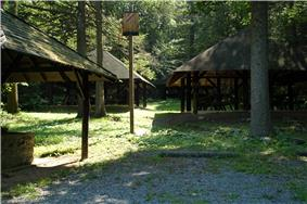 Three rustic picnic shelters in a forest