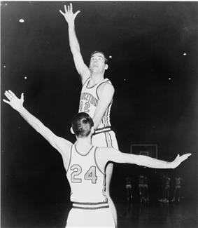 A basketball player, with the number 42 on his short-sleeved uniform, leaping high into the air with his right hand stretched upward.  He is being guarded by another player with the number 24 on his shirt