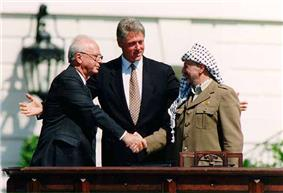 A man in a dark suit on the left shakes the hand of a man in traditional Arab headdress on the right. Another man stands with open arms in the center behind them.