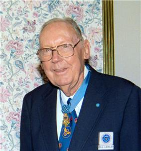 Elderly white man wearing a suit, tie, and glasses, with a medal hanging from a ribbon around his neck.