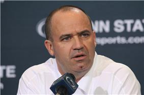 A man in a white shirt (Penn State coach Bill O'Brien) sits in front of a blue background with the words