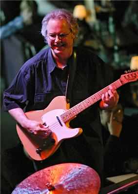 A man wearing glasses, playing a guitar and standing behind a cymbal.