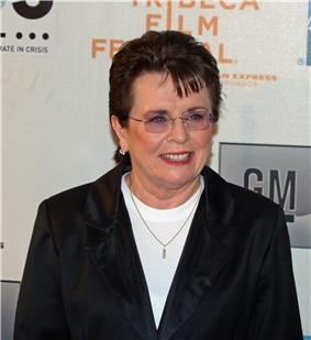 A brown haired women in a black jacket and white shirt