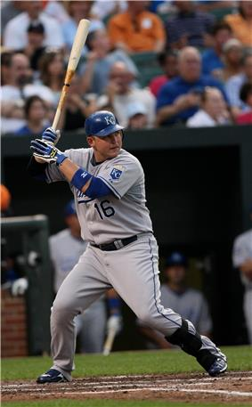 A man in a gray baseball uniform and blue batting helmet prepares to swing in a right-handed batting stance.