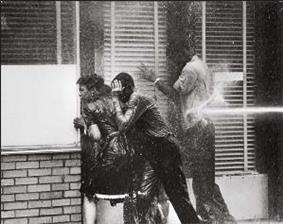 Three black high school students, two boys and a girl, facing into a storefront window to avoid being hurt by a water cannon Blasting of boy at his back; all three are dripping with water