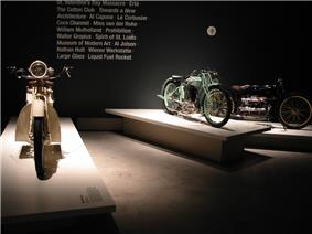 Three pristine 1920s - 1930s motorcycles on pedestals in front of text printed on the wall with words relevant to the period, such as