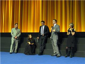 Scott Franklin, Mila Kunis, Vincent Cassel, Darren Aronofsky, and Sandra Hebron stand on a stage with a golden curtain backdrop wearing formal attire and discussing Black Swan