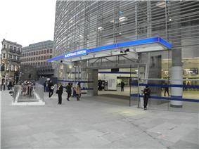 A glass structure with gray slats on higher floor; an entrance leads under a canopy with a sign reading