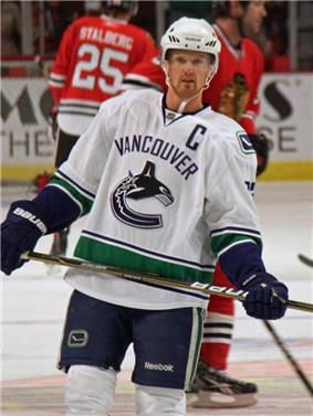 An ice hockey player wearing a white and blue jersey with a logo of a stylized orca in the shape of a