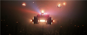 A screenshot from the film shows a line of police vehicles with flashing lights flying high above a smog-covered cityscape. Below them several small pinpoints of light from aircraft-avoidance lights on the tops of towers are all that can be seen of the city