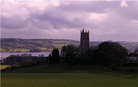Church tower surrounded by trees with water in the background.