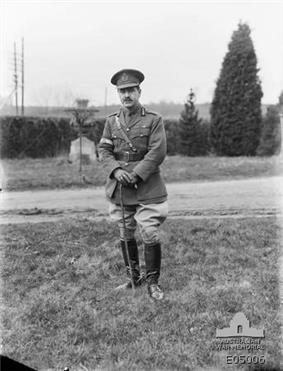 A man in a neat military uniform with a peaked cap, ribbons on his tunic, Sam Brown belt, cane, riding boots and spurs.