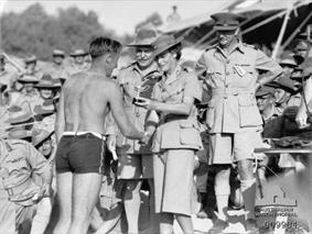 A large crowd of men in uniforms with slouch hats. A woman in uniform with skirt and flat bush hat presents a small trophy to a man in a swim suit.