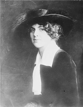 Upper body portrait of Blanche Oelrichs, sitting side on, turning her face to the camera
