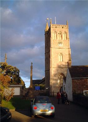 Square three stage stone tower. To the right is a building with a white wall and in the foreground a parked car.