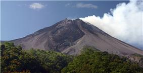 A photograph depicting a blue sky with white clouds at the top, a dark grey volcano in the middle, and green foliage at the bottom.
