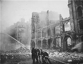 Historical photograph of a building severely damaged by air-raid bombing; firefighters are putting out a blaze in the ruins.