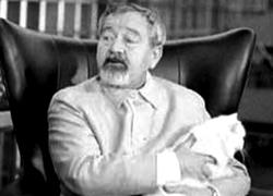 Upper body shot of a middle aged man with short, greying hair, moustache and goatee, holding a cat in his arms.