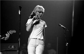 A black and white photograph of Debbie Harry on stage with a microphone