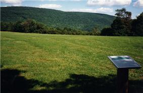 A green mountain in the background with a grassy hill and a sign in the foreground</center>