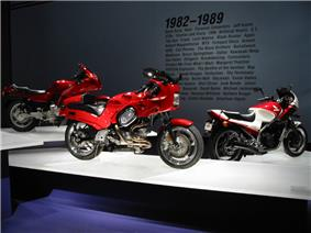 Three sporty motorcycles of the 1990s on pedestals.  Text on the wall behind them says