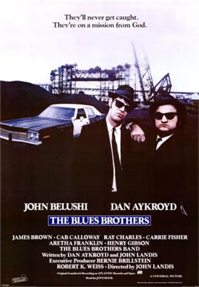 Movie poster with two of the main characters on the right-side of the image: They are both wearing black suits, hats, and sunglasses and facing forward. The man on the right is resting his arm on the shoulder of the man on the left. A police car is present on the left side of the image behind them. At the top of the image is the tagline,