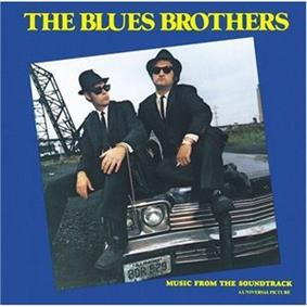 The two main characters are sitting on the hood of a car, wearing black suits, hats, and sunglasses. The man on the left is looking to his left and has a handcuffed chain on his left wrist attached to a briefcase. The man on the right is holding a cigarette in his left hand and has his right leg tucked underneath the other. On the border of the image is a blue frame, with