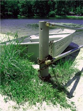 A metal rowboat chained to a metal pole with a lake behind