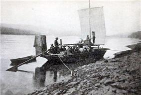 Prospectors sailing toward Dawson in boat on upper Yukon River, 1898
