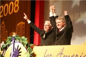 Bob Barr stands on a stage with another grey-haired man, both are smiling and holding each other's arms up in victory