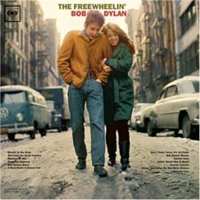 The Freewheelin' Bob Dylan's album cover. Wearing a brown jacket and blue jeans, a man walks along a snowy street. A woman wearing a long green coat and black pants holds onto his arm and walks alongside him. The words