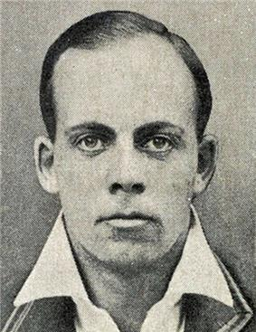 A head shot of a man in a blazer.