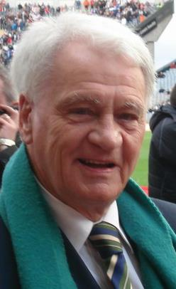 An elderly man with grey hair smiling at the camera. He is in a football stadium and is wearing a black suit with a multi-coloured tie and a green scarf.