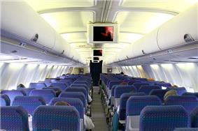 Airliner cabin. Rows of seats arranged between a center aisle.  There are overhead monitors.