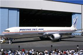Side quarter view of twin-engine jetliner in front of hangar, with surrounding crowds.