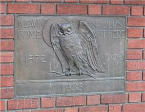 Plaque showing an owl, the moon, and text