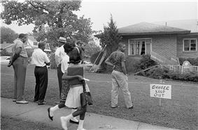 A black and white photograph of a suburban house with minor bomb damage to the roof and two windows while five black Birmingham residents stare at the damage; the yard is cordoned off with a sign saying