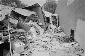 A black and white photograph of a building in ruins next to an intact wall
