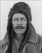 A man with moustache in a winter coat with a hat covering his ears.