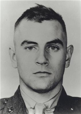 Head of a white man in a military jacket with dark hair, short on the sides and slightly longer, and ruffled, on top.