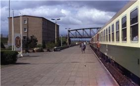 View of a train stopped at a long railway platform, at the end of which is an arched iron bridge. A grey concrete barracks and East German state emblem are visible on the side of the platform. Several people are standing or walking on the platform and the train's doors stand open.