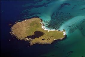 An island seen from above sits in a dark green water and sandy shallows. The island has some sandy beaches and contains a body of water that makes up about a sixth of its area.