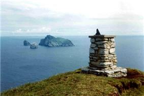 A stone trigonometric point, composed of individual stones cemented together into a small structure about a metre high and with a small metal object on the top, possibly a sundial, sits at the summit of a high hill. It overlooks an ocean in which there are three distant islands. One is large, green and wedge-shaped. The other two are precipitous stacks.